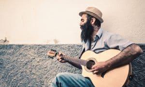man playing and singing guitar at the same time